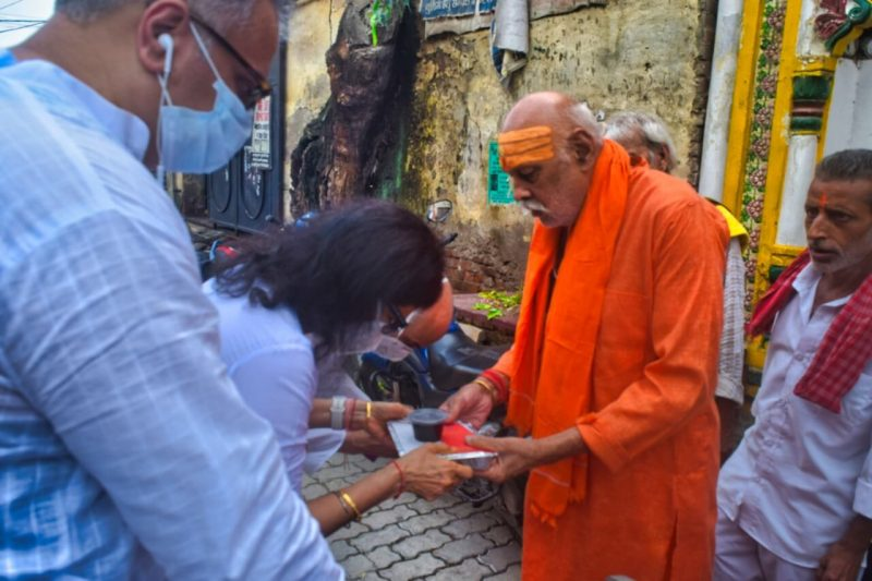 A lady donating food material to a priest